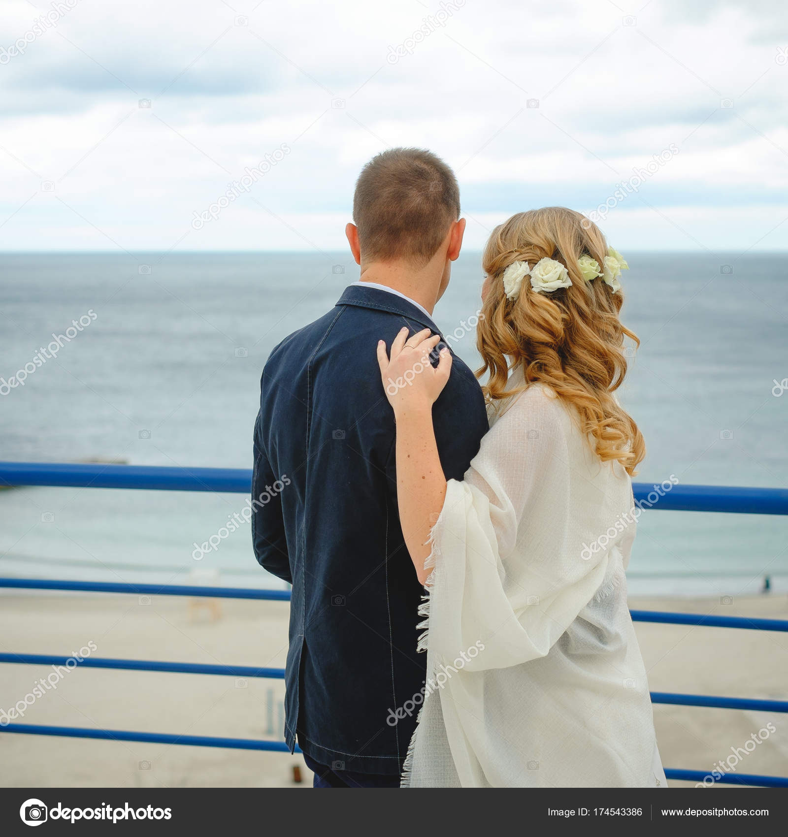 c3ba43d506a7 Ζευγάρι στην αγάπη νεαρή νύφη και τον γαμπρό ντυμένος στα λευκά αγκάλιασμα  στο γκρεμό φόντο γαλάζιο στην ημέρα του γάμου τους– εικόνα αρχείου