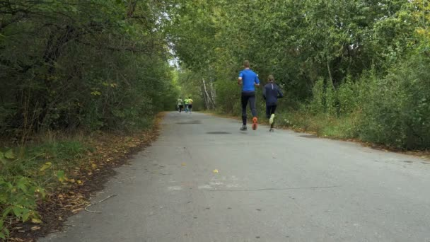 group of young runners running down road in city autumn Park