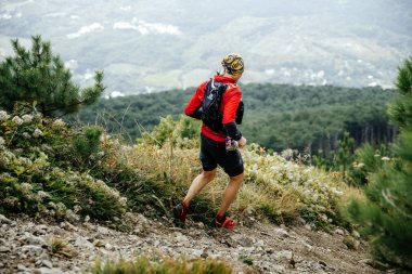Male athlete marathon runner running with mountains along trail