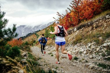 two athletes runners running from mountain along trail in autumn landscape
