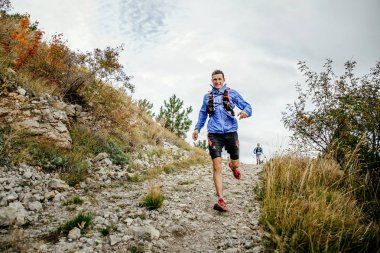 Male runner of middle age runs on a mountain trail