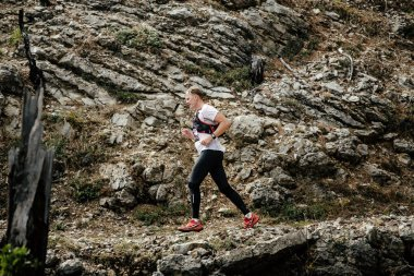 Young runner runs on a mountain trail in background stone rocks