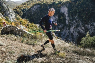 young male runner with walking poles running through steep cliff