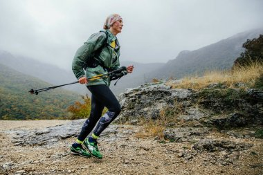 Runner middle-aged woman running in rain on a mountain trail with walking poles