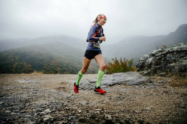 Young girl runner running in rain in compression socks and running backpack