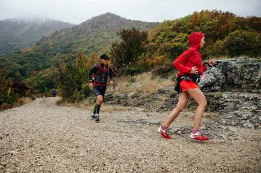 young man and woman runners athletes run on a mountain trail