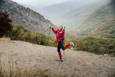 young girl tourist with walking sticks fooling around on a mountain trail in rain