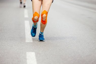 feet girl runner injury kinesiotape knee running on street
