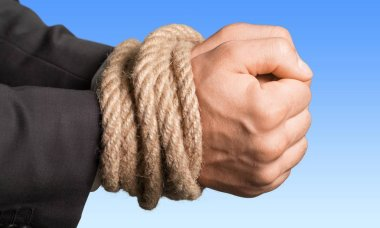 Businessman hands tied with rope