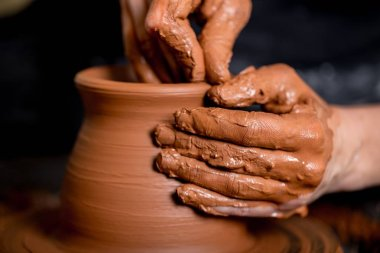 hands of potter making clay pot