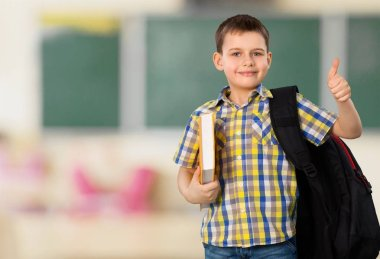 school boy with book and backpack