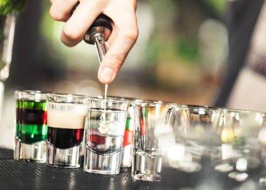barman pouring liquor to shot cocktails