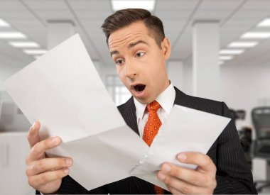 shocked businessman looking at paper