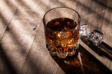 Glass of whiskey and ice isolated