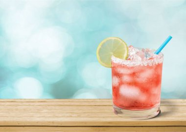 delicious pink cocktail with ice and lemon