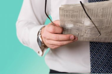 glasses and newspaper in man hand