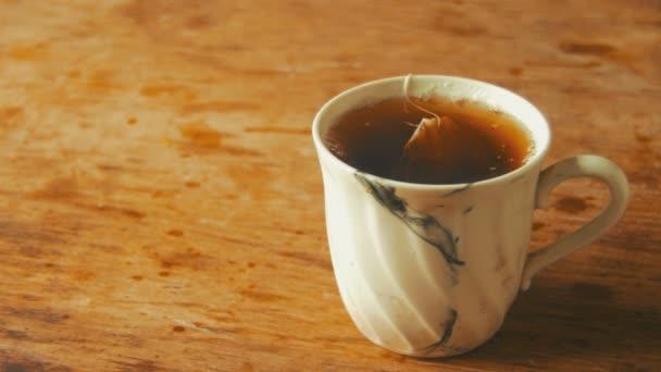 Hrnek s čajem na dřevěný stůl