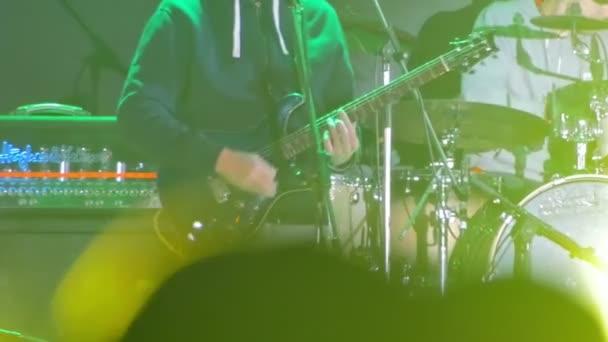 Kytarista hraje na jevišti na rockový koncert