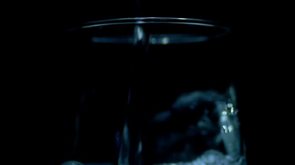 Water is Poured into a Transparent Glass on the Black Background. Slow Motion