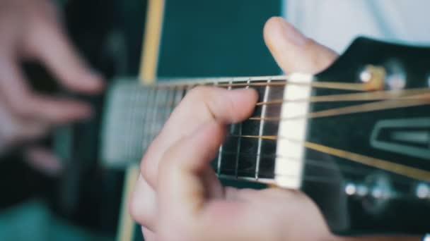 muž hrající na akustickou kytaru
