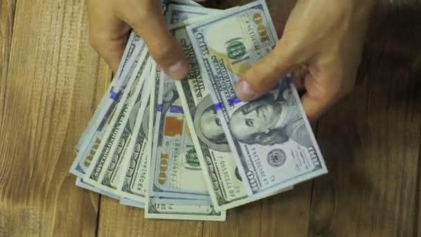 Muž ruce uvažovat dolarové bankovky na dřevěný stůl.