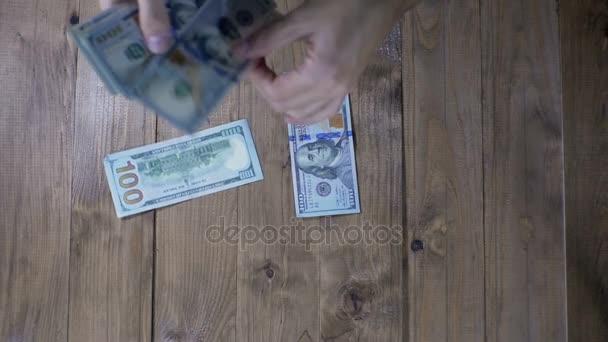 Dolarové bankovky na dřevěný stůl. Zpomalený pohyb