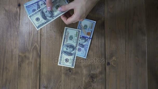 Muž ruce za dolarové bankovky na dřevěný stůl. Zpomalený pohyb