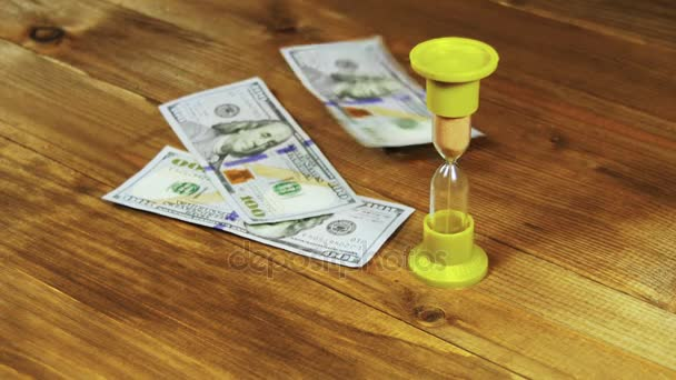 Dolarové bankovky na dřevěný stůl a přesýpací hodiny