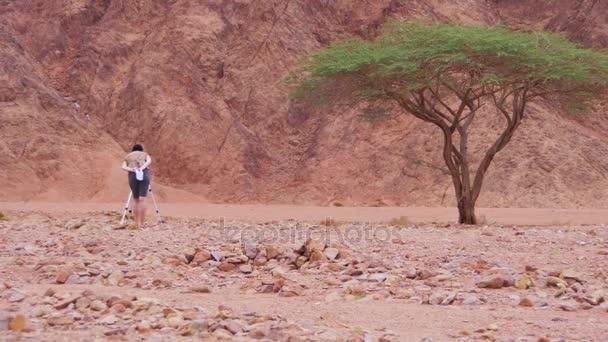 Žena filmaře se stativem v egyptské pouště.
