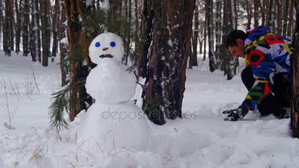 Man Making Snowman in Pine Forest, add White Snow and Finish Beautiful Snowman