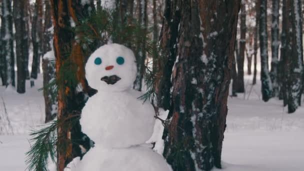 Mann im Kiefernwald formt Schneemann