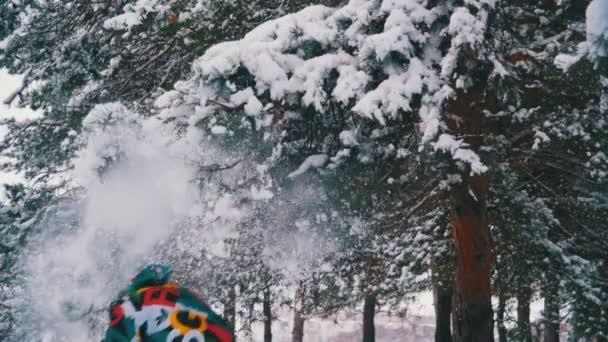Mann rennt und wirft den Schnee mit schneebedeckten Ästen in den Winterwald. Zeitlupe