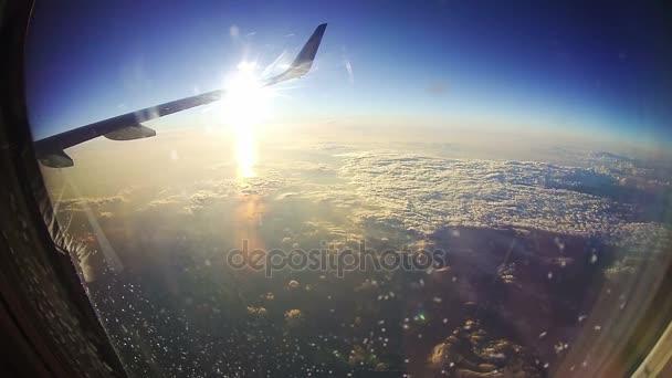 Pohled z okna letadla nad mraky na pozadí slunce