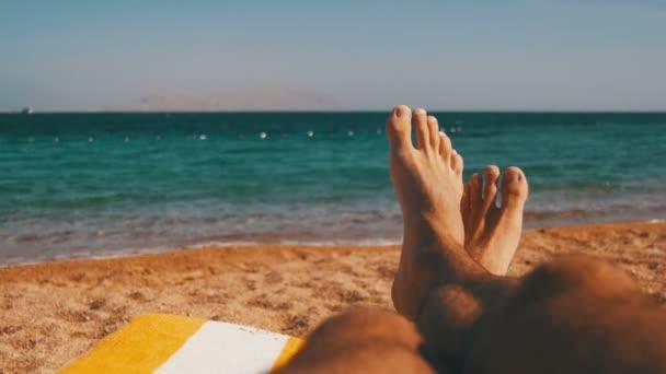 Nohy muž ležící na lehátku na pláži u moře