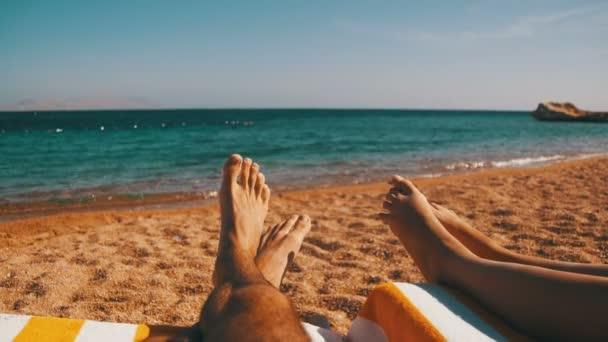 Nohy z pár lidí ležet na lehátku na pláži u Rudého moře