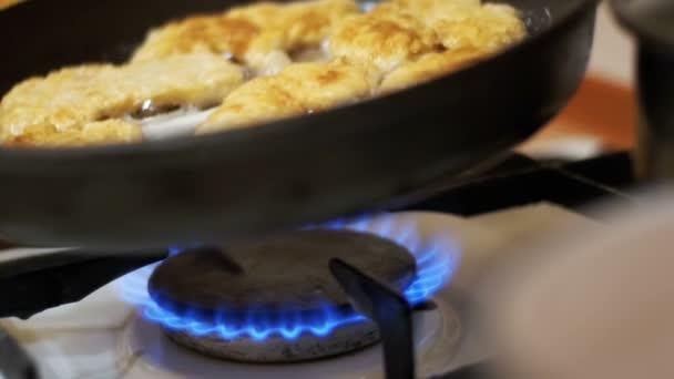 Egy serpenyőben az otthoni konyhában a hús sütés karaj. Lassú mozgás