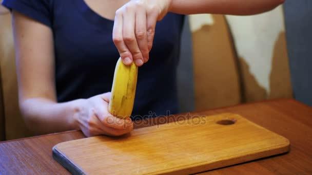 Woman Cleaning a Banana While Sitting at a Table in a Home Kitchen