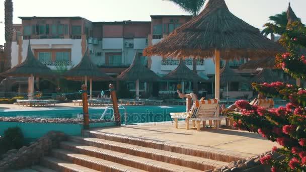 Sonnigen Resort-Hotel mit blauen Pool, Palmen und Sonnenliegen in Ägypten