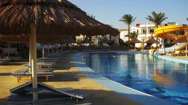 sonniges Hotelresort mit blauem Pool, Palmen und Sonnenliegen in Ägypten