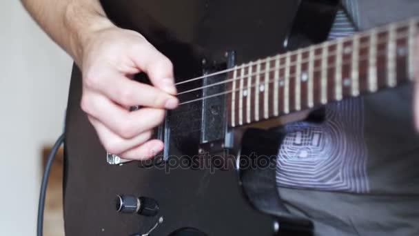 Kytarista hraje elektrickou kytaru v domácím studiu