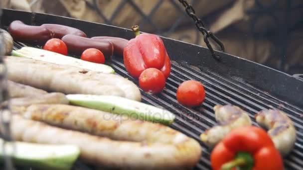 Vaření chutné grilované klobásky a zeleniny na grilu. Zpomalený pohyb