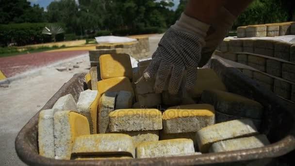 Staveniště, stavební dělník se uvolní, dlažební kámen z koše. Zpomalený pohyb
