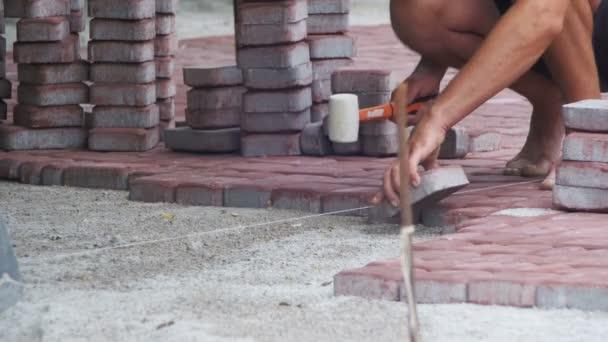 Pracovník je pokládka dlažby pomocí kladivo