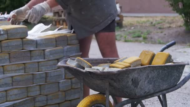 Pracovník načte barevné dlažební vozí na trakaři