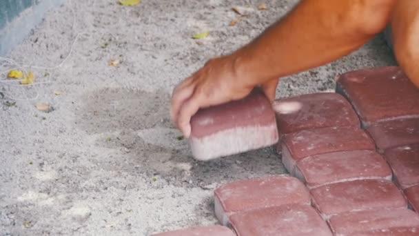Pracovník, kterým se kámen dlažební desky. Zpomalený pohyb