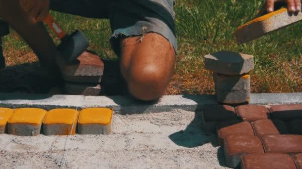 Munkavállaló a tojásrakás útburkoló kövek használó Hammer