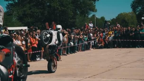 Moto-Stuntshow. Moto-Fahrer fährt auf das Hinterrad. Biker-Parade und Show. Slow-Motion