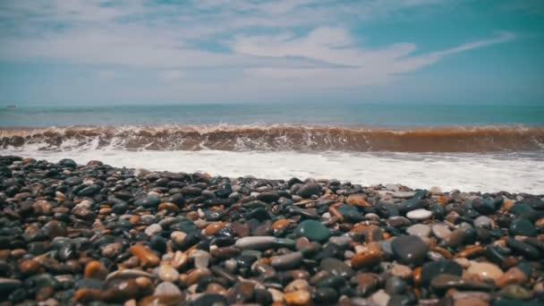 Vihar a tengeren. A hullámok gurul a kő kavicsos strandon. Lassú mozgás
