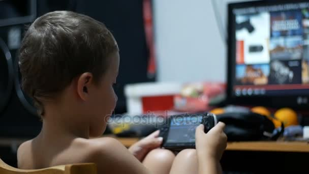 8 Years Old Kid Playing Video Games on a Portable Game Console Sitting on a Chair at Home