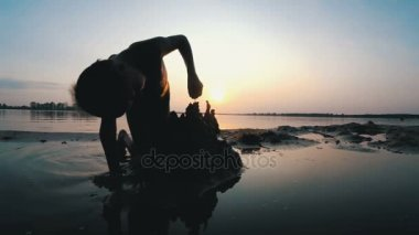 Silhouette of a Child on the Beach Building a Sand Castle at Sunset